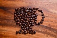 一杯咖啡在木背景的豆 库存照片