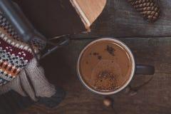 一杯咖啡在木背景的 电烙与毛线衣和一本旧书的篮子 定调子 免版税图库摄影