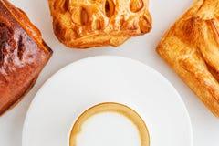 一杯咖啡在板材和小圆面包的在白色背景 免版税库存图片