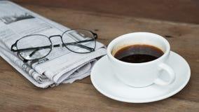 一杯咖啡在桌上的与报纸 免版税库存图片