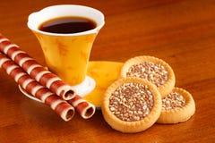 一杯咖啡在桌上的立场与可口甜点 库存图片