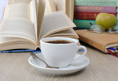 一杯咖啡在桌上的以开放b为背景 免版税库存照片