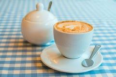 一杯咖啡在桌,一个糖罐上的在背景中 Se 库存图片