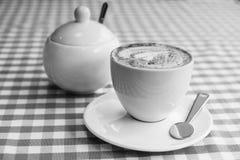 一杯咖啡在桌,一个糖罐上的在背景中 Se 免版税库存照片
