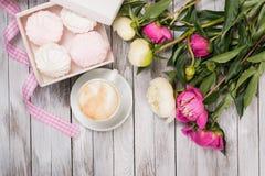 一杯咖啡在牡丹、一个箱子用蛋白软糖和桃红色丝带旁边花束的在木背景 顶视图 免版税库存图片