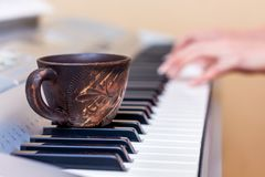 一杯咖啡在钢琴钥匙的 在插入式放大器期间的咖啡消耗量 库存图片