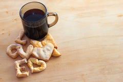 一杯咖啡烘烤透明杯子的曲奇饼爱木背景 库存照片