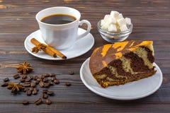 一杯咖啡用在板材的肉桂条和鲜美蛋糕片断  在白色的豆早餐咖啡理想的查出的宏指令 有糖立方体和茴香的一个碗在木头 免版税库存照片