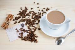 一杯咖啡用桂香和咖啡豆在一张木桌上 库存图片