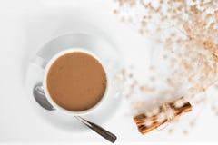 一杯咖啡用桂香和咖啡豆在一张白色桌上 免版税库存图片