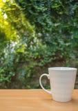 一杯咖啡的一张选择聚焦图片在木桌上的在绿色庭院里 库存照片