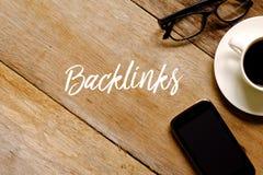 一杯咖啡的顶视图、手机和镜片在木背景写与BACKLINKS 库存照片