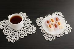 一杯咖啡的顶视图和五颜六色的土耳其快乐糖用在鞋带餐巾的杏仁染黑桌 免版税库存照片