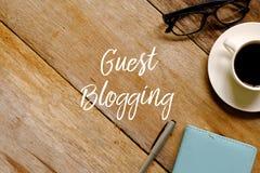 一杯咖啡的顶视图镜片、笔记本和笔在木背景写与BLOGGING的客人 免版税图库摄影