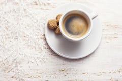 一杯咖啡,在白色木背景的雪花 图库摄影
