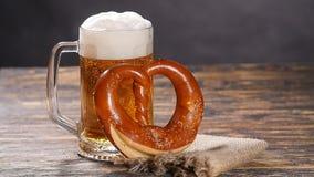 一杯啤酒和椒盐脆饼在一张木桌上 股票视频