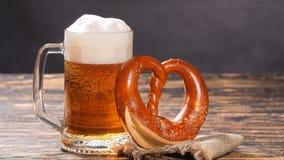 一杯啤酒和椒盐脆饼在一张木桌上 股票录像
