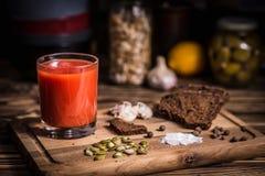一杯在一个木板的西红柿汁用黑麦面包 图库摄影
