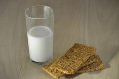 一杯在一张木桌上的牛奶用小面包干薄脆饼干 免版税库存照片