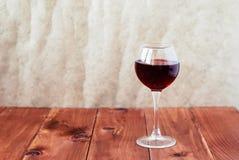 一杯在一张木表的红葡萄酒 库存照片