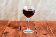 一杯在一张木表的红葡萄酒 库存图片