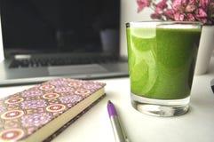 一杯在一张桌上的新鲜的绿色圆滑的人与便携式计算机、桃红色笔记本、笔和一棵桃红色盆的植物 免版税库存图片