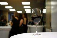 一杯在一张白色桌上的红葡萄酒在一个运作的办公室 免版税库存图片
