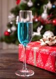一杯在圣诞树的背景的蓝色香槟 库存图片