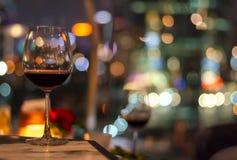 一杯在屋顶酒吧桌上的红酒  免版税库存图片