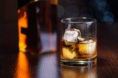 一杯在岩石的威士忌酒和在桌上的一个瓶 库存图片