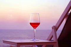 一杯在日落海背景的红葡萄酒 浪漫日期co 免版税库存照片