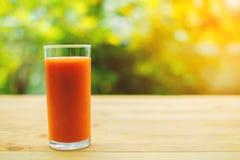 一杯在木桌上的西红柿汁 库存图片