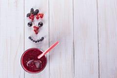 一杯在白色背景的莓果圆滑的人 从莓果的微笑 饮食食物概念 免版税库存照片