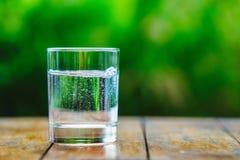 一杯在绿色背景的水 库存图片