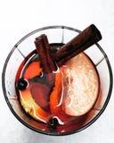 一杯在雪的加香料的热葡萄酒 库存照片