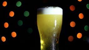 一杯在黑背景的冰镇啤酒与色的光 啤酒在玻璃起泡沫 股票录像