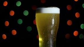 一杯在黑背景的冰镇啤酒与色的光 啤酒在玻璃起泡沫 HD 股票视频