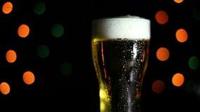 一杯在黑背景的冰镇啤酒与色的光 水流量下落在玻璃下的 假日的心情 股票视频