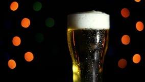 一杯在黑背景的冰镇啤酒与色的光 水流量下落在玻璃下的 假日的心情 影视素材