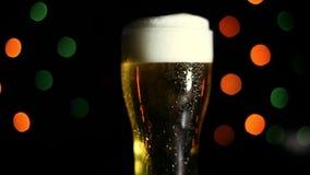 一杯在黑背景的冰镇啤酒与色的光 水流量下落在玻璃下的 股票视频