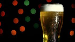一杯在黑背景的冰镇啤酒与色的光 HD 股票录像