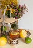 一杯在玻璃持有人、有些甜点、成熟柠檬和石灰的红茶反对轻的背景的亚麻制表面上 免版税图库摄影