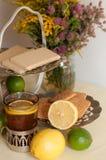 一杯在玻璃持有人、有些甜点、成熟柠檬和石灰的红茶反对轻的背景的亚麻制表面上 库存图片