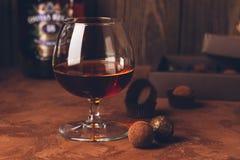 一杯强的酒精饮料白兰地酒或白兰地酒和一箱在黑暗的背景的巧克力 复制空间 免版税库存照片