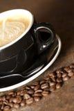 热奶咖啡和接近的咖啡豆 免版税库存照片