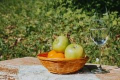 一杯新鲜的苹果计算机水和苹果在一个篮子在一张木桌上 免版税图库摄影