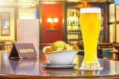 一杯未过滤的啤酒用面包干乳酪,片剂-是后备的在餐馆酒吧的一张木桌上 库存照片