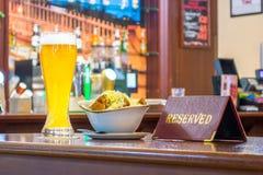 一杯未过滤的啤酒用面包干乳酪,片剂-是后备的在餐馆酒吧的一张木桌上 免版税图库摄影