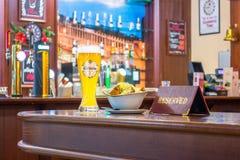 一杯未过滤的啤酒Edelweiss用面包干乳酪,片剂-是后备的在餐馆酒吧的一张木桌上 俄国 Mo 免版税库存图片