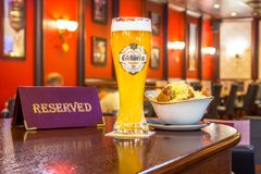 一杯未过滤的啤酒Edelweiss用面包干乳酪,片剂-是后备的在餐馆酒吧的一张木桌上 俄国 Mo 免版税库存照片